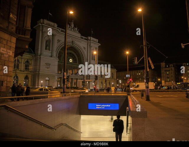 BUDAPEST, HUNGARY - APRIL 6, 2018: Man going down the stairs of a metro Station in front of Budapest Keleti Palyaudvar train station at night  Picture - Stock Image