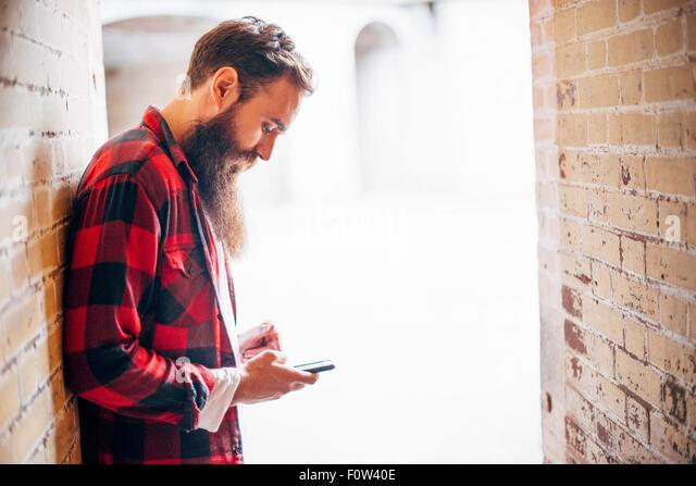 Side view of man with beard holding smartphone - Stock-Bilder