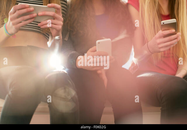 Teenage girls texting with cell phones in a row - Stock Image