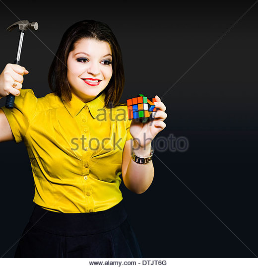 Short-sighted junior employee who has not thought through the implication of her actions raises a hammer with glee - Stock Image