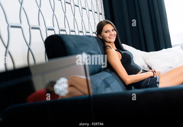 Beautiful young woman in a hotel room smiling - Stock Image