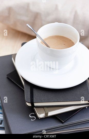 Cup of coffee on stack of books - Stock Image