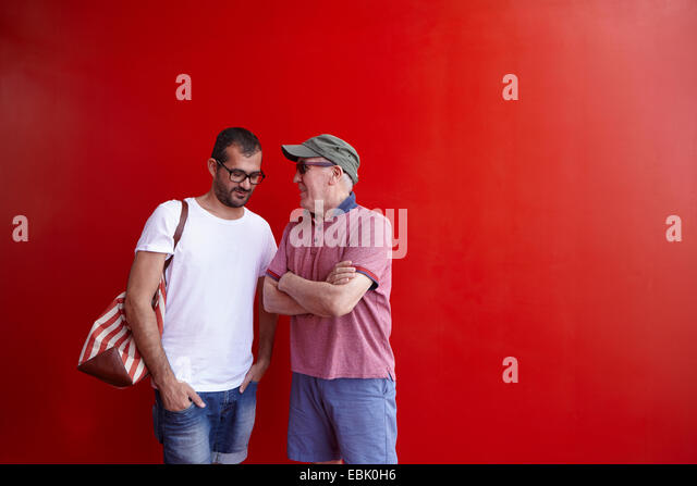 Mid adult man and senior man talking, standing against red background - Stock Image