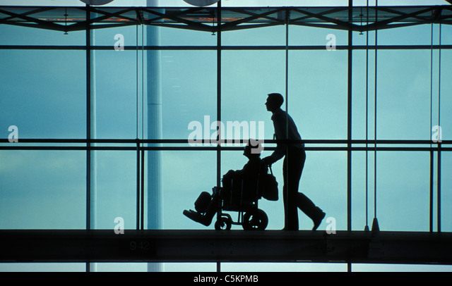Silhouette of young man pushing old lady in a wheelchair on a raised walkway, Aberdeen Airport, Scotland - Stock Image