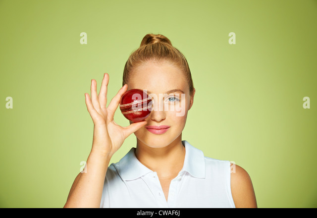 Young woman holding cricket ball over her eye - Stock Image