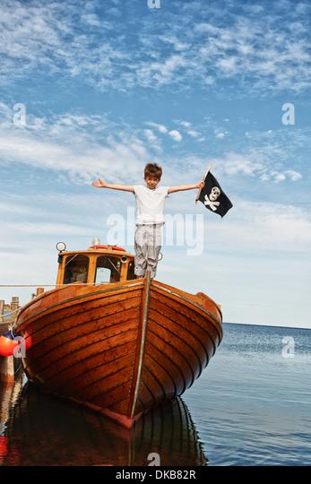 Portrait of boy on boat holding pirate flag, Eggergrund, Sweden - Stock Image