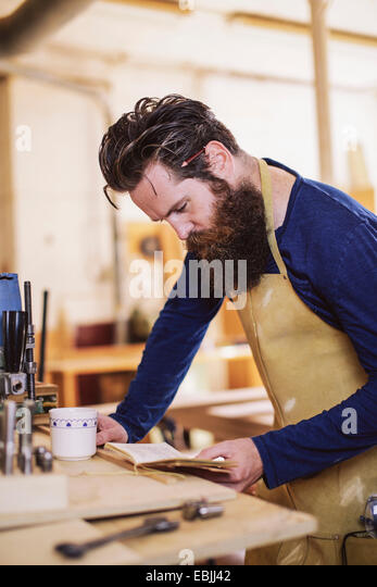 Mid adult craftsman checking notebook in organ workshop - Stock Image