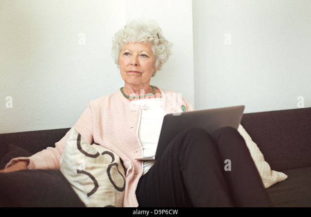 Cheerful senior lady smelling a flower indoors - Stock Image