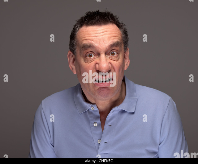 Middle Age Man Pulling Funny Grimace Face on Grey Background - Stock Image
