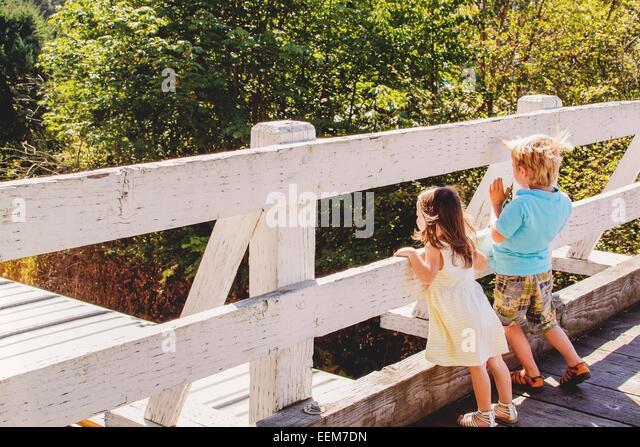Young boy (4-5) and girl (2-3) watching train on bridge - Stock Image