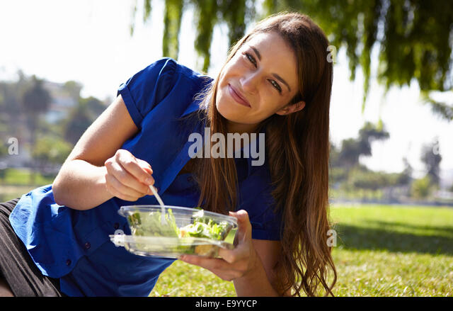 Woman eating salad in park - Stock Image