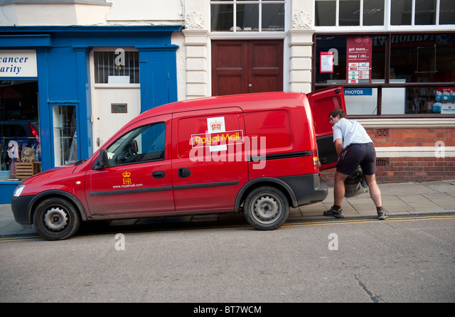 A postman loading a sack of mail into his van UK - Stock Image