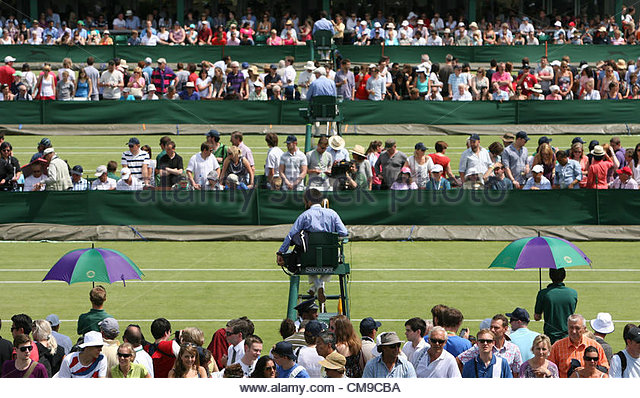 28/06/2012 - Wimbledon (Day 4) - Umbrellas go up to shade the players as spectators surround the outside courts - Stock-Bilder
