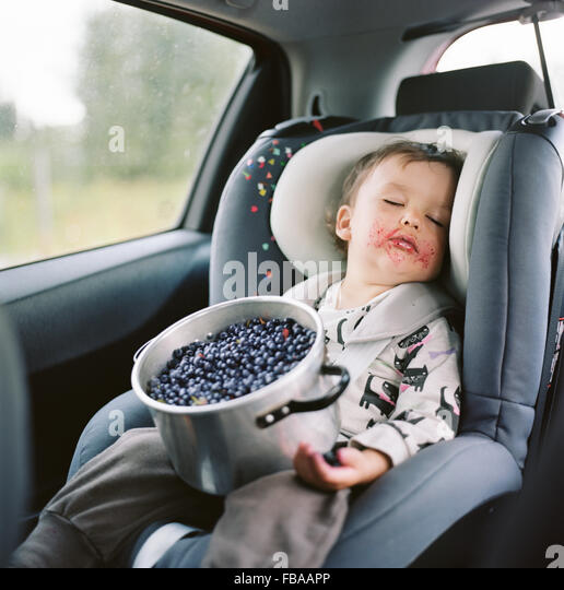 Finland, Uusimaa, Lapinjarvi, Portrait of girl (2-3) sleeping in car seat with pot full of blueberries on lap - Stock Image