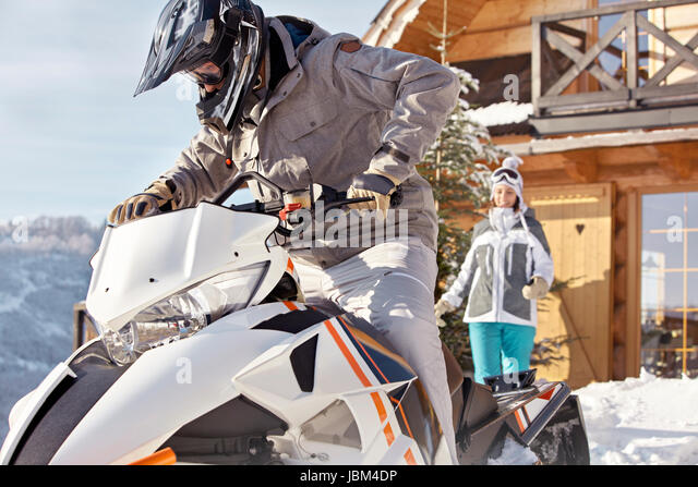 Couple riding snowmobile outside sunny cabin - Stock-Bilder