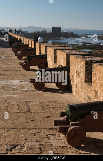A line of old cannons guard the walls of the town of Essaouira in Morocco - Stock Image