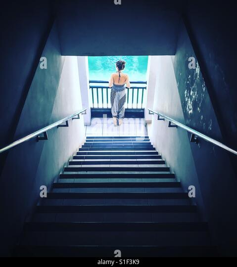 A woman standing poolside at the bottom of a dark stairwell. Light from the blue swimming pool shines and reflects - Stock-Bilder