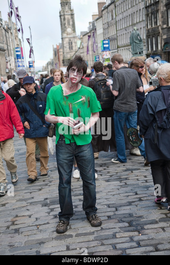 Edinburgh festival fringe actor dressed as a zombie handing out publicity flyers on the Royal Mile - Stock Image