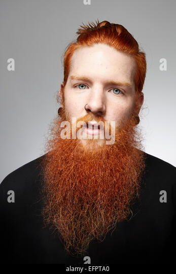 Studio portrait of staring young man with red hair and overgrown beard - Stock-Bilder