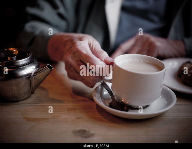 Old ladies hands holding cup of tea. - Stock-Bilder