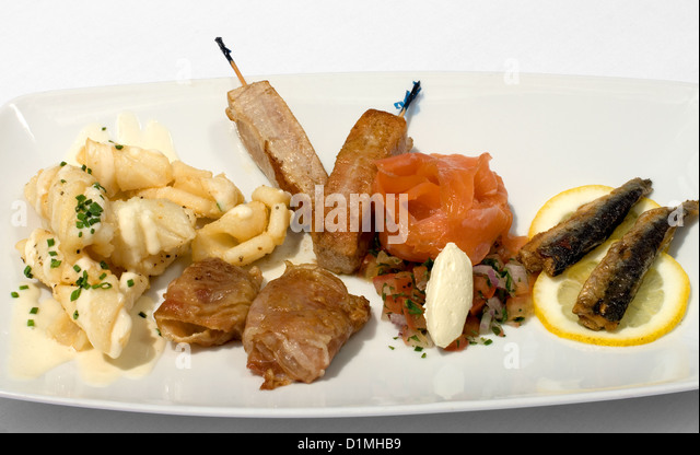 An Entree of Salt & Pepper Squid with Aioli, Tuna skewers,  Sardines, Porsciutto-wrapped Scallops, and smoked - Stock Image