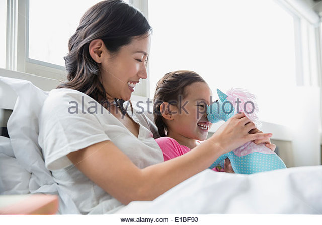 Mother and daughter with stuffed animal in bed - Stock-Bilder