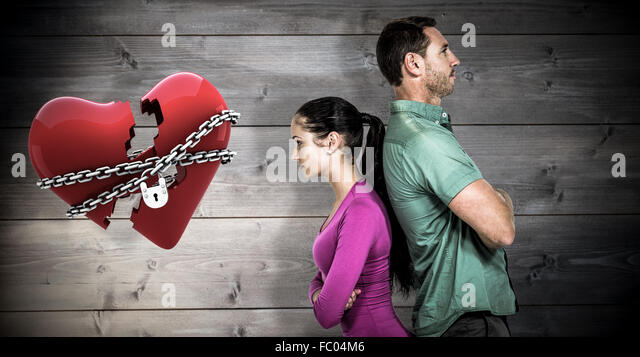 Composite image of couple standing back to back - Stock Image