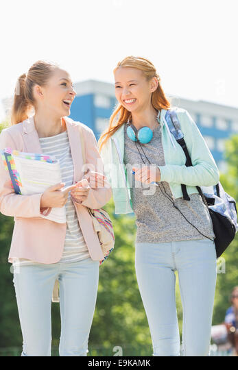 Cheerful young female college students walking in campus - Stock Image