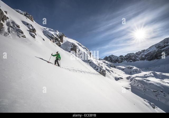 Austria, Male skier heading uphill - Stock Image