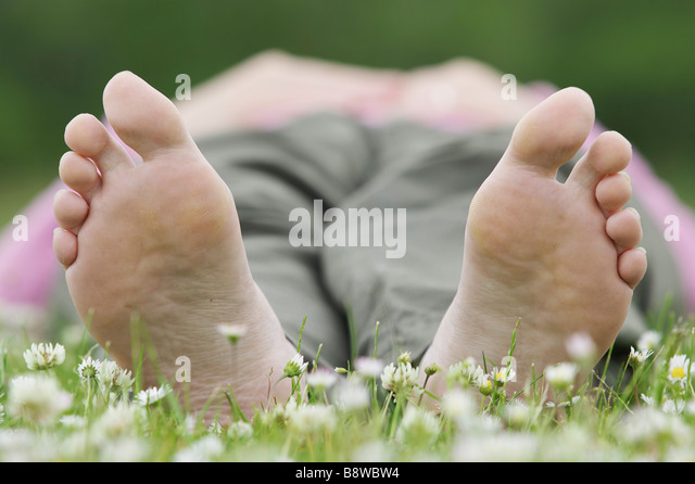 Close up of undersides of bare feet of woman lying on grass - Stock-Bilder
