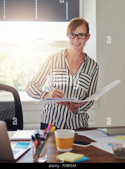 Woman working at office holding papers - Stock Image