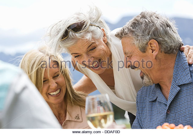 Mature friends having fun at an outdoor picnic - Stock Image