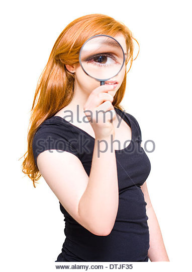 Woman Holding Looking Glass Or Magnifying Glass Up To Eye To Enlarge A Clue While On A Search For Research Analysis - Stock Image