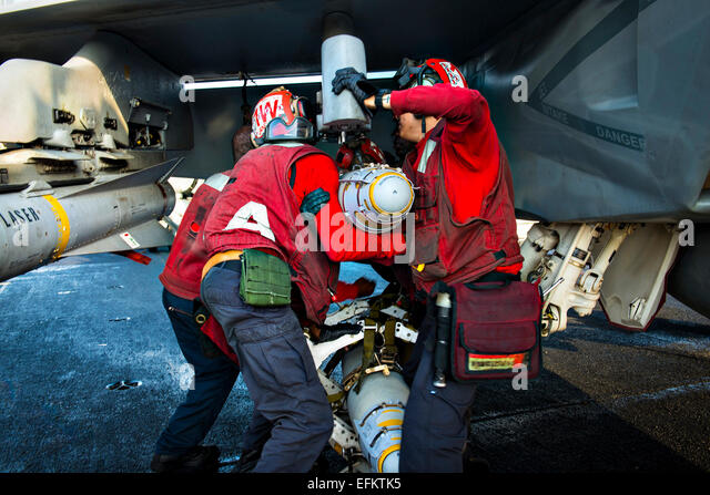 US Navy sailors load a Mk 82/Blu 500 pound bomb onto an F/A-18F Super Hornet fighter aircraft on the flight deck - Stock Image