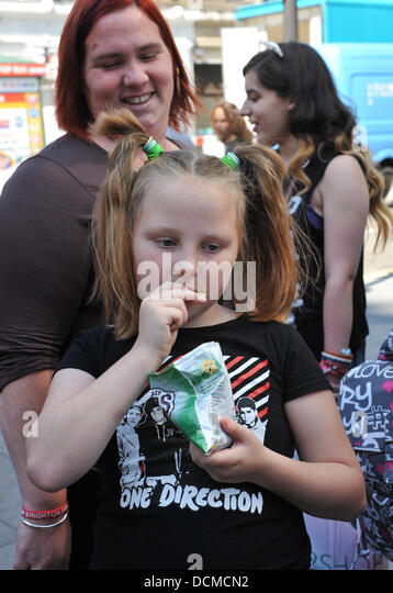 Leicester Square, London, UK. 20th August 2013. Mother and daughter, fans of boy band One Direction queue to get - Stock Image