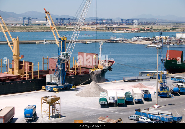 Trucks, Cranes and Ships loading salt,  Cagliari Harbour, Sardinia, Europe, truck lorry wait waiting at Cagliari - Stock Image