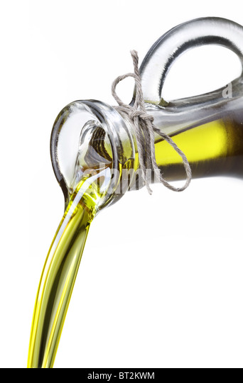 Olive oil flowing from carafe into the spoon isolated on a white. - Stock Image