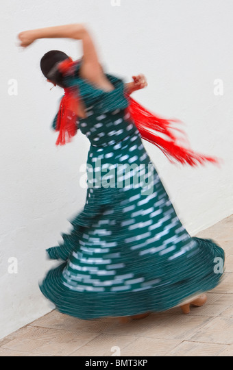 Motion blurred slow shutter speed shot of woman traditional Spanish Flamenco dancer spinning & dancing in green - Stock Image