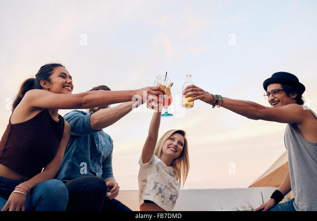 Happy friends celebrating the success with a toast at rooftop party. Young men and women toasting cocktails at party. - Stock Image