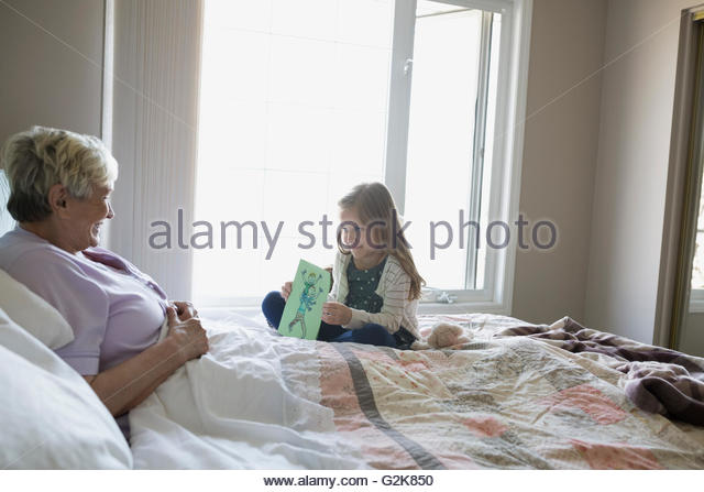 Granddaughter showing handmade drawing to grandmother in bed - Stock Image