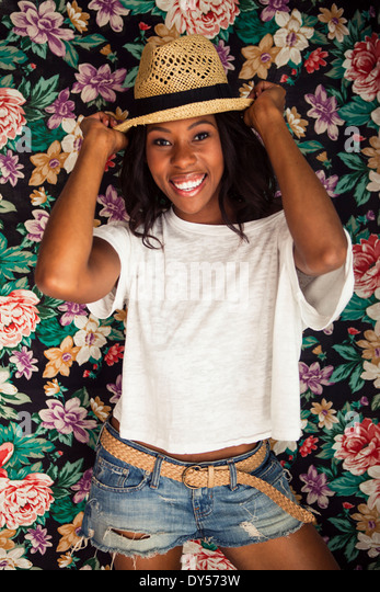 Young woman wearing straw hat in front of floral wallpaper - Stock Image