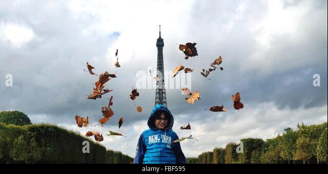 Low Angle View Of Boy Standing Against Eiffel Tower - Stock-Bilder
