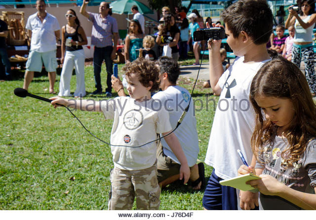 Miami Beach Florida South Pointe Elementary School PTA Green Market Fundraiser booth vendor boy girl student microphone - Stock Image