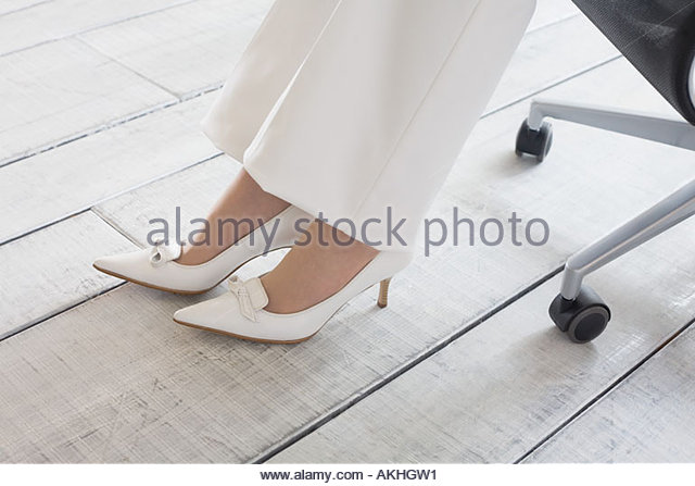 Woman wearing white shoes and trousers - Stock Image
