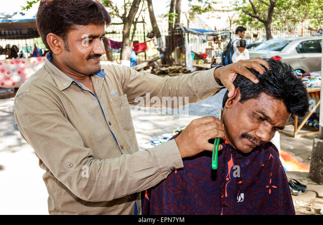 India Asian Mumbai Karmaveer Bhaurao Patil Marg Mantralaya Fort Mumbai sidewalk barber shaving customer man - Stock Image