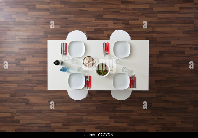 A table with place settings, wine, water, salad and bread, no people, overhead view - Stock Image
