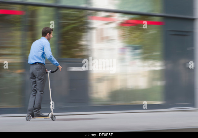Man in business attire riding on push scooter - Stock Image