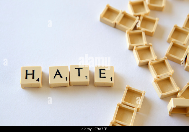 Scrabble tiles / squares spell out emotion word HATE, white background studio photograph - Stock Image