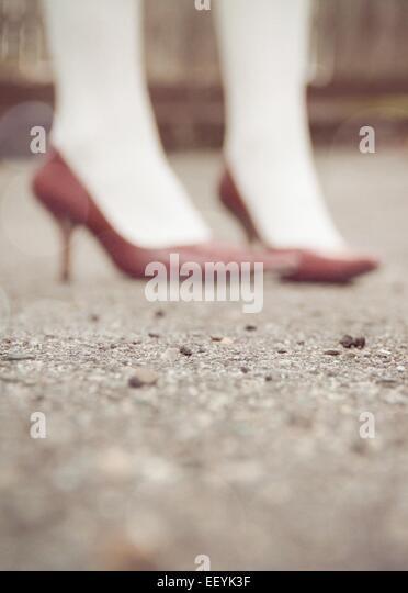 Portrait of women's feet wearing red high heels. - Stock-Bilder