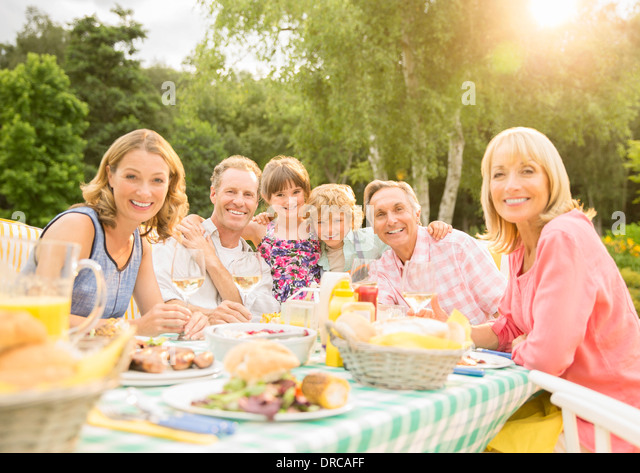 Multi-generation family enjoying lunch at table in backyard - Stock Image